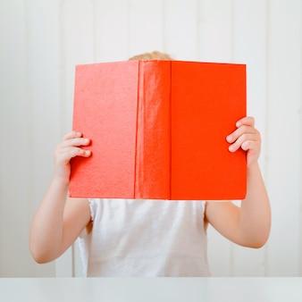 Libro di lettura carino bambina, che copre il viso.
