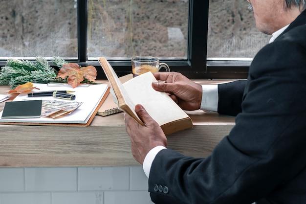 Libro di lettura del direttore aziendale e caffè bevente.