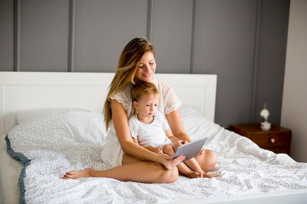 Libro di lettura del ragazzino e della madre sul letto nella camera da letto