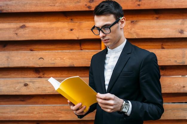 Libro di lettura del ragazzo isolato su backround di legno