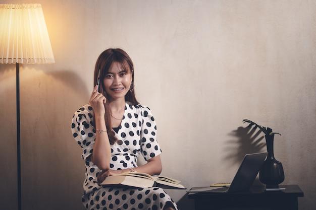 Libro di lettura della donna dell'asia nel tempo libero con felice