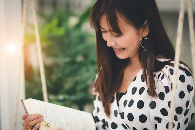 Libro di lettura della donna dell'asia nel tempo libero con felicità
