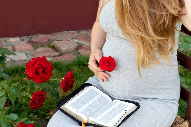 Libro di lettura della donna incinta (bibbia) in giardino. aspettando il bambino.