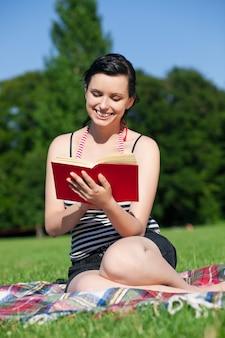 Libro di lettura della donna sul prato