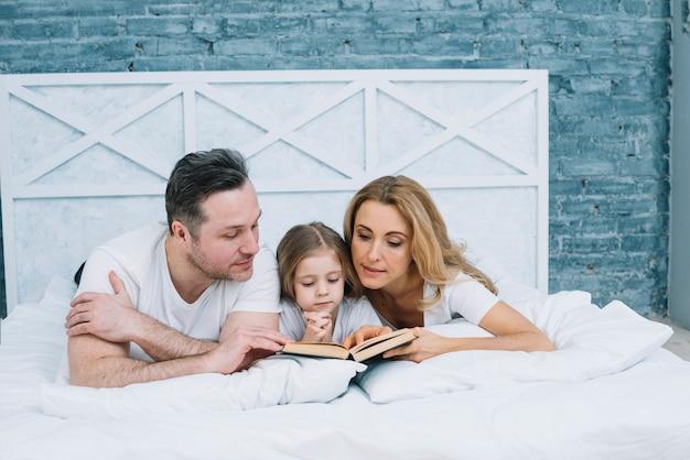 Libro di lettura della famiglia sul letto