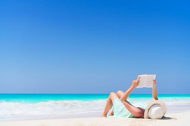 Libro di lettura della giovane donna durante la spiaggia bianca tropicale