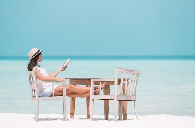 Libro di lettura della giovane donna durante la spiaggia delle maldive tropicale