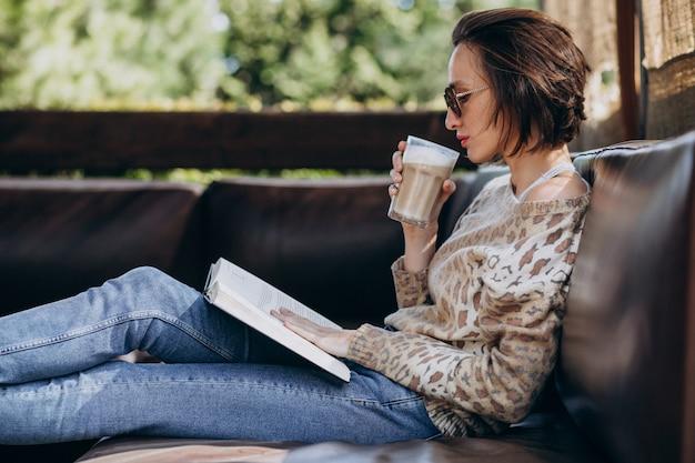 Libro di lettura della giovane donna e caffè bevente