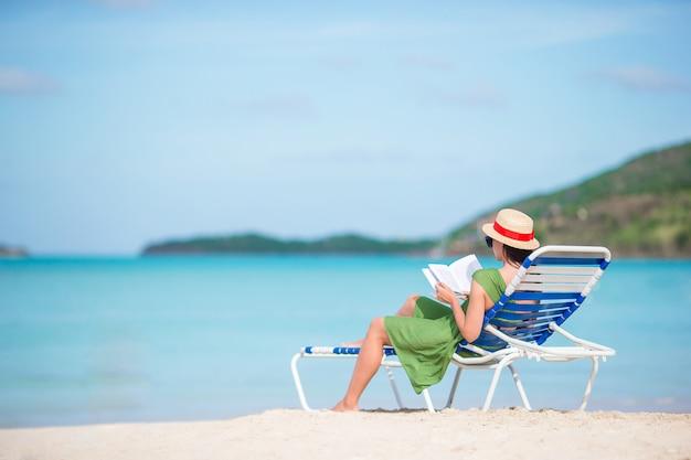 Libro di lettura della giovane donna sulla chaise longue sulla spiaggia
