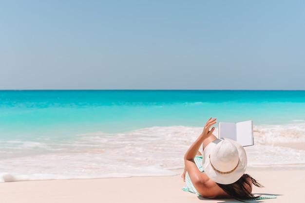 Libro di lettura della giovane donna sulle chaise longue sulla spiaggia
