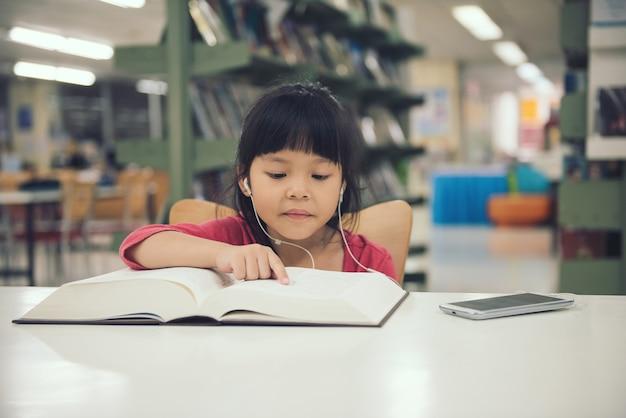 Libro di lettura della ragazza dei bambini alla stanza della biblioteca