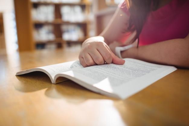 Libro di lettura della studentessa nella biblioteca dell'istituto universitario