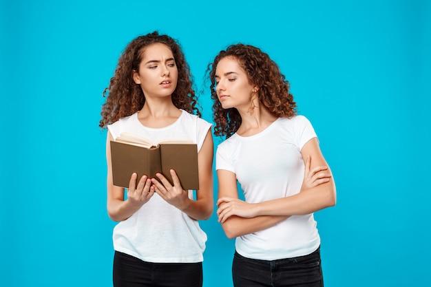 Libro di lettura di due gemelli della donna sopra il blu.