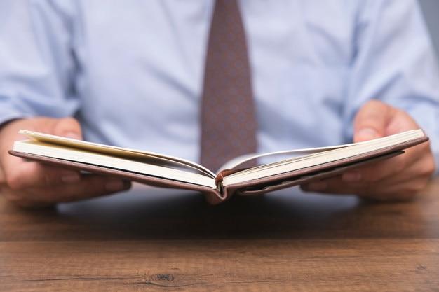 Libro di lettura di uomo d'affari sul tavolo