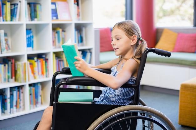 Libro di lettura disabile della ragazza della scuola in biblioteca