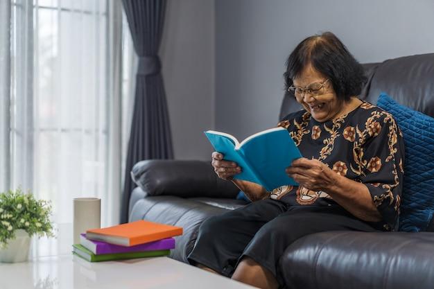 Libro di lettura donna senior e ridendo nel salotto