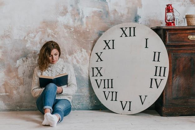 Libro di lettura donna vicino al disco dell'orologio