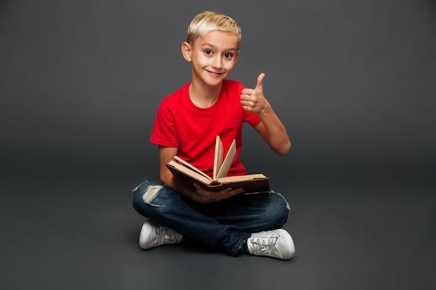Libro di lettura felice del bambino del ragazzino che mostra i pollici in su.