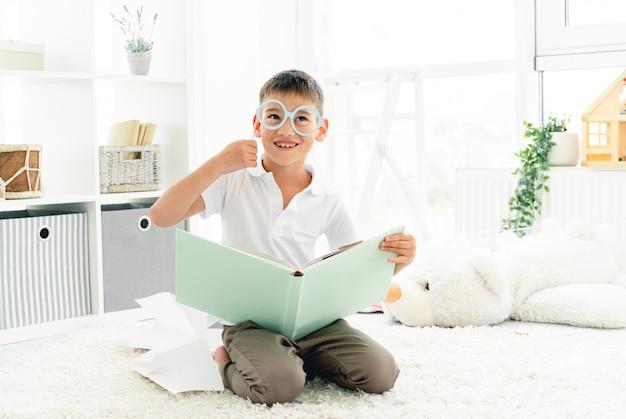 Libro di lettura felice del ragazzo con gli occhiali