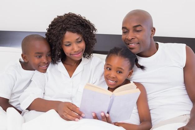 Libro di lettura felice della famiglia insieme a letto