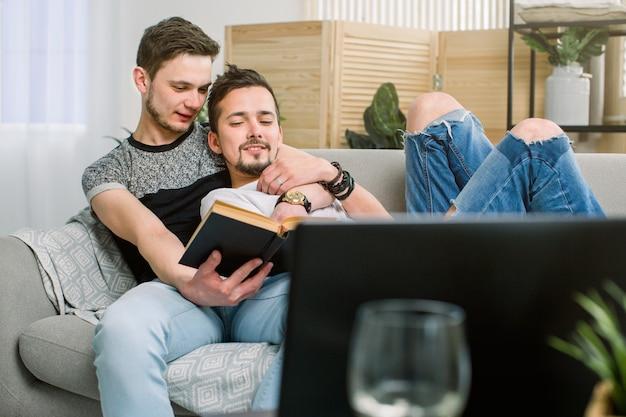 Libro di lettura gay attraente delle coppie sul sofà a casa in salone