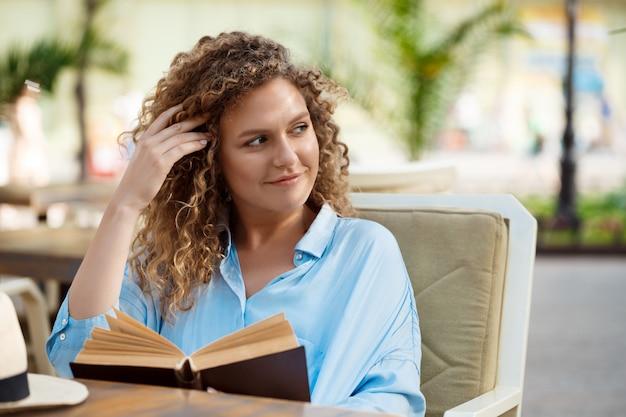 Libro di lettura giovane bella ragazza, seduto in un caffè.