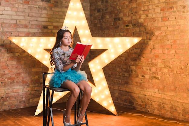Libro di lettura grazioso della ragazza davanti alla grande stella illuminata contro il muro di mattoni