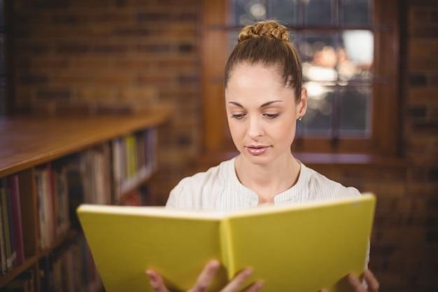 Libro di lettura insegnante bionda in biblioteca