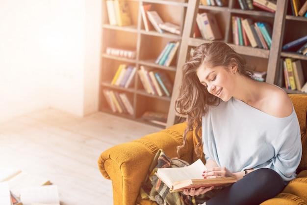 Libro di lettura nella stanza soleggiata della biblioteca