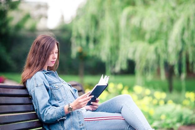 Libro di lettura rilassato della giovane donna all'aperto nel parco