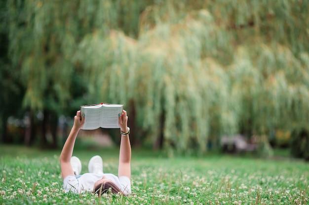 Libro di lettura rilassato della giovane donna nel parco