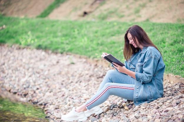 Libro di lettura rilassato della giovane donna