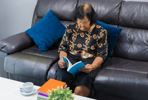 Libro di lettura senior della donna in salone