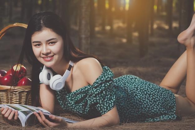 Libro di lettura sexy della donna dell'asia, ascoltante la musica nel tempo libero con felice.