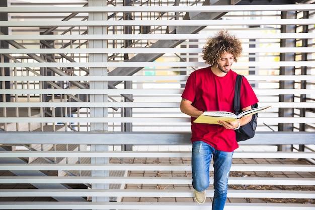 Libro di lettura sorridente dell'uomo vicino alla parete