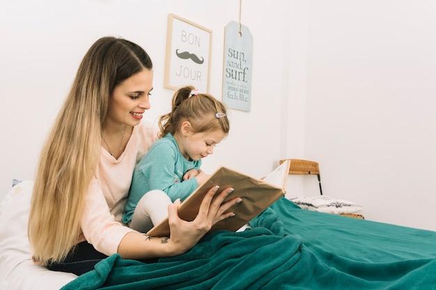 Libro di lettura sorridente della donna alla figlia a letto