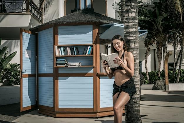 Libro di lettura sorridente della donna vicino alla palma