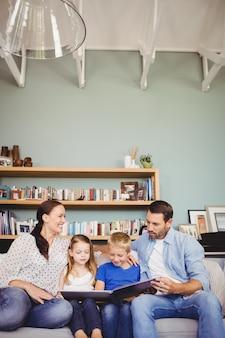 Libro di lettura sorridente della famiglia mentre sedendosi sul sofà