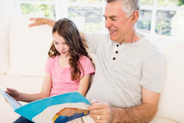 Libro di lettura sorridente della nipote e del nonno sul sofà