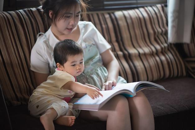 Libro di lettura sveglio del bambino con sua mamma