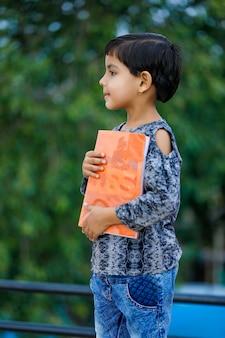 Libro di scuola indiano sveglio della tenuta del bambino