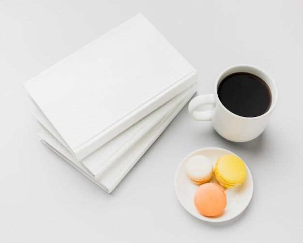 Libro di vista superiore con caffè e macarons sulla scrivania