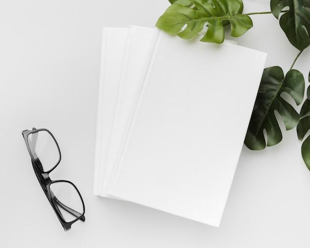 Libro di vista superiore con occhiali e foglie sulla scrivania