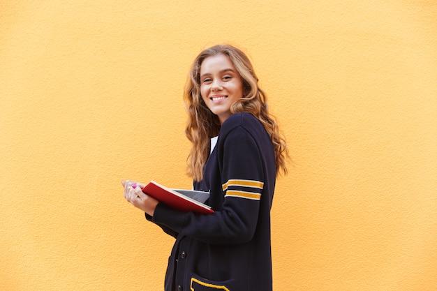 Libro e sguardo sorridenti graziosi della tenuta dell'adolescente