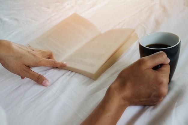 Libro e una tazza di caffè sul letto