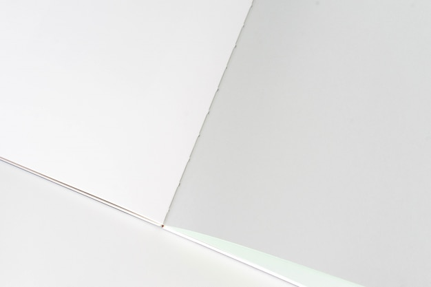 Libro in bianco aperto al fondo grigio bianco della carta di progettazione.