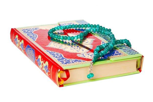 Libro islamico sacro corano e perline su bianco