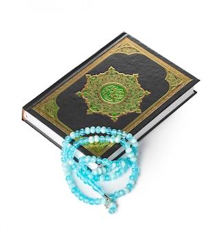 Libro islamico sacro corano e perline su sfondo bianco
