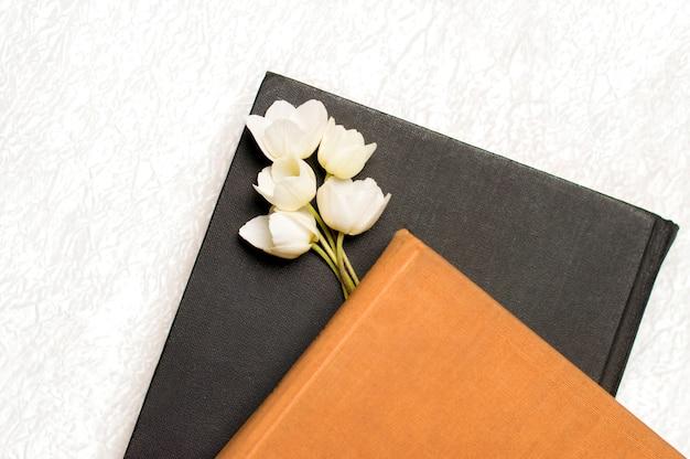Libro nero e marrone con fiori su un bianco