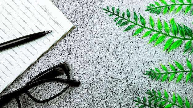 Libro, penna e un bicchiere sulla scrivania di cemento. - per lo sfondo del concetto creativo e aziendale.